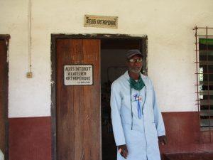 Doyen Paul devant l'entrée de l'atelier orthopédique